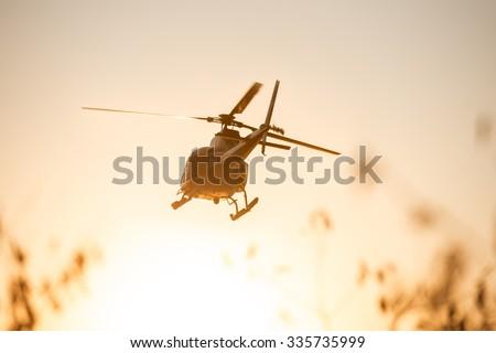 Passenger Helicopter flying in sunset sky - stock photo