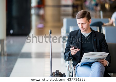 Passenger in an airport lounge waiting for flight aircraft. Young man with cellphone in airport waiting for landing - stock photo