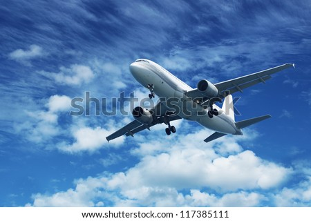 Passenger jet air plane flying on blue sky white clouds background - stock photo