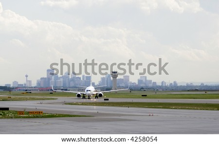 Passenger jet being directed to runway with city in background - stock photo