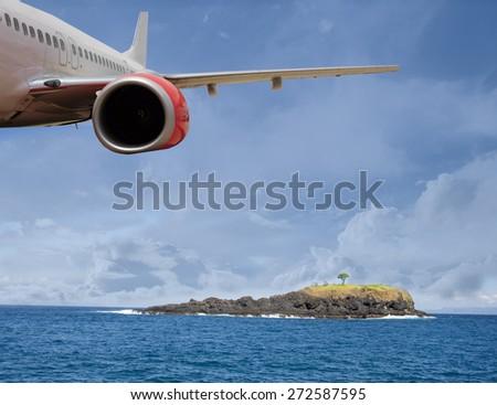 Passenger Jet Plane Flying Above tropical Island for travel concept - stock photo
