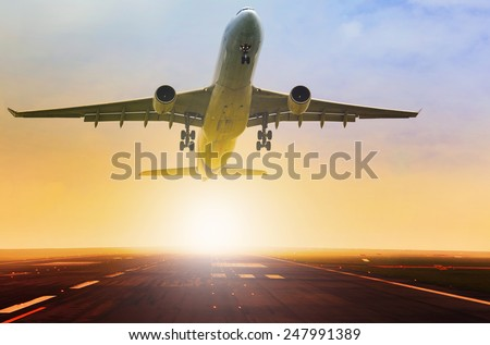 passenger jet plane take off from airport runway with beautiful light of sun rising behind - stock photo