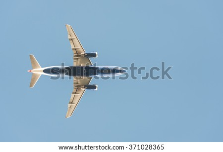 passenger jet silhouette against a clear blue sky - stock photo