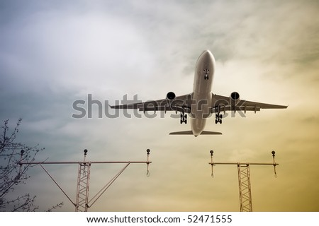 passenger jet taking-off or landing through color gradient clouds - stock photo