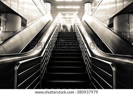 Passenger on moving escalator at subway station in Shanghai, Blur abstract. - stock photo