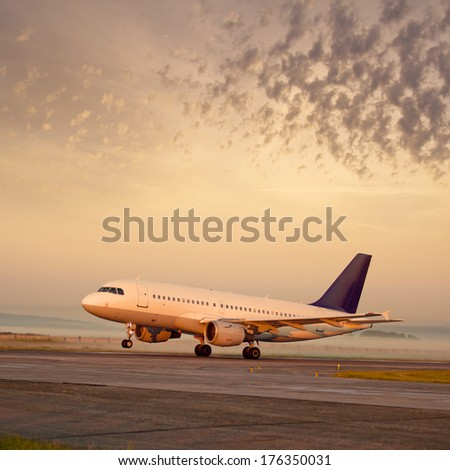 Passenger plane about to take off at dawn - stock photo