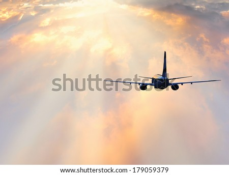 Passenger plane above the colorful clouds. - stock photo