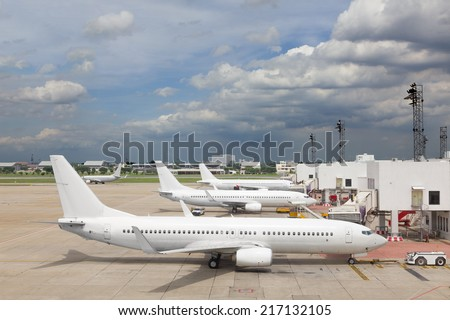 Passenger plane at airport near boarding terminal - stock photo