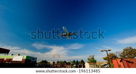 passenger plane fly down over take-off runway from airport  - stock photo