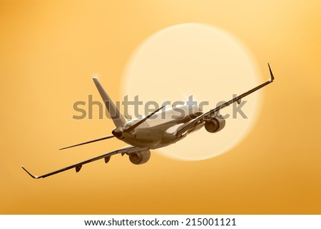 passenger plane fly down over take-off runway from airport at sunset - stock photo