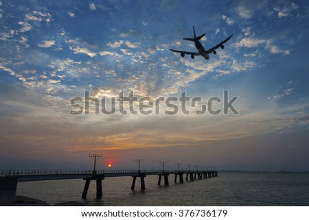 passenger plane fly up over take-off runway from airport at suns - stock photo