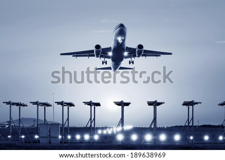 passenger plane fly up over take-off runway from airport at sunset - stock photo