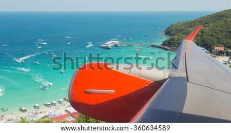passenger plane flying over beautiful blue sky and island  - stock photo