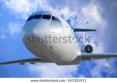 passenger plane in the blue cloudy sky