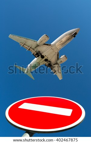 Passenger plane in the blue sky. Aircraft is flying over the road sign «do not enter». - stock photo