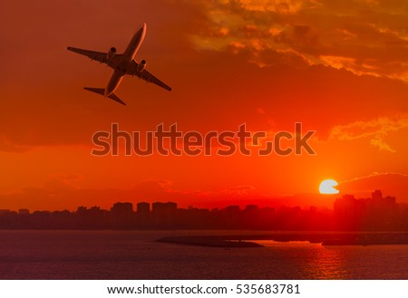 Passenger plane is landing away from airport at sunset