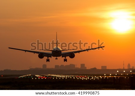 Passenger plane is landing during a wonderful sunrise.