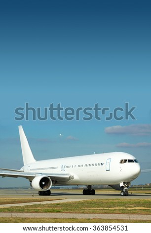 Passenger plane on the runway and another jet is taking off on the background - stock photo