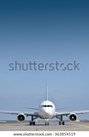 Passenger plane on the runway in the airport - front view on a sunny day - stock photo
