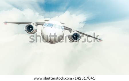Passenger plane with cockpit and engines in front view flying high in blue cloudy sky. Comfortable and fast travelling by air. Business and touristic trips. Aviation and aircraft. - stock photo