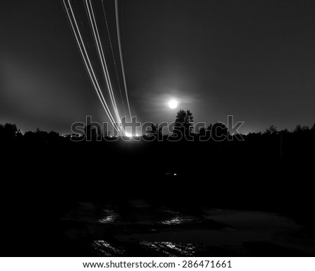 Passenger planes take off from runways against beautiful night sky with moon. Long exposure. Motion blur, and light trace - stock photo