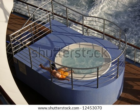 Passenger relaxing in a jacuzzi pool on the deck of a cruiseship - stock photo