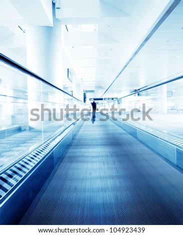 passenger rushing through an escalator in airport terminal - stock photo