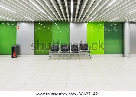 Passenger seat in a green glass hall - stock photo