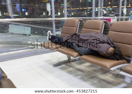 Passenger sleep on a bench in airport terminal waiting for his flight