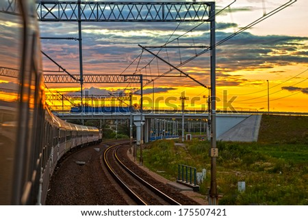 Passenger train on the railway at the sunset.  - stock photo