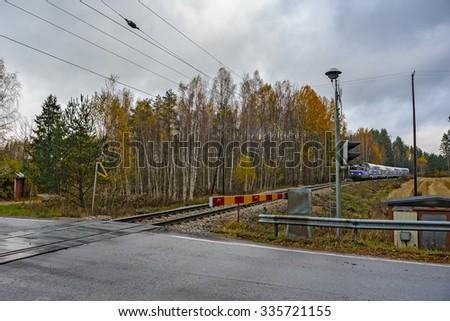 Passenger train passing a railway crossing - stock photo