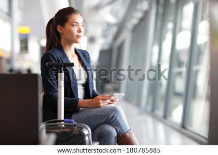 Passenger traveler woman in airport waiting for air travel using tablet smart phone. Young business woman smiling sitting with travel suitcase trolley, in waiting hall of departure lounge in airport. - stock photo