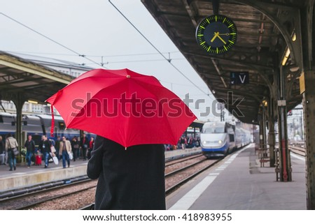 passenger waiting for the train on the platform of railway station - stock photo