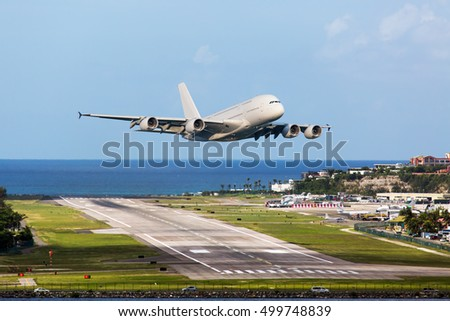 Passenger wide body aircraft. The plane takes off from the airport runway. The blue sea in the background.