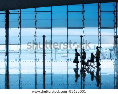 passengers and disabled person in the interior of the airport - stock photo