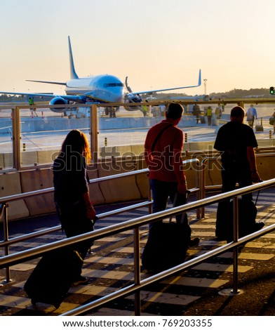 Passengers boarding airplane at an airport at sunset