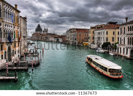Passengers boat passing by old venetian houses along the Grand Canal in Venice, Italy.