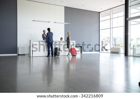 Passengers departing from business trip at hotel reception  - stock photo