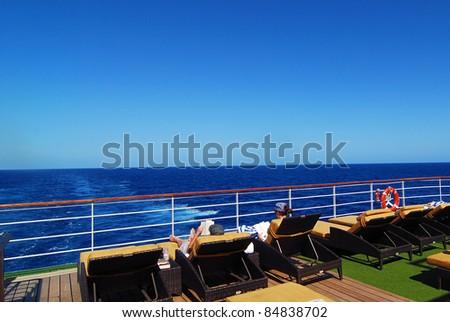 passengers enjoy sunshine on a cruise ship with blue ocean background - stock photo