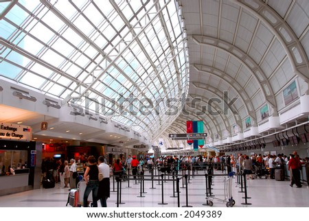 Passengers lining up at check-in counter at the modern international airport - stock photo