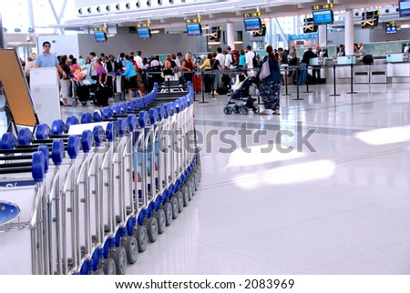 Passengers lining up at the check-in counter at the modern international airport - stock photo