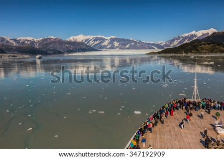 Passengers on Cruise ship looking at glacier. - stock photo