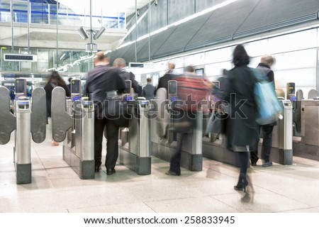 Passengers passing through automatic ticket barriers at underground Station, zoom effect - stock photo