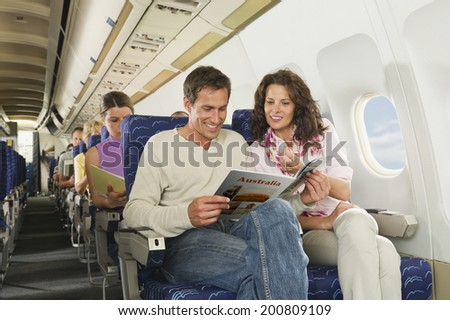 Passengers reading book on airplane - stock photo