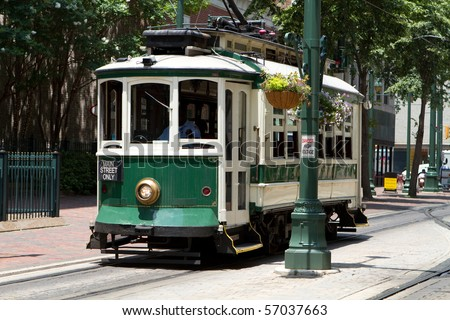 Passengers ride an electric trolley car down Main Street.
