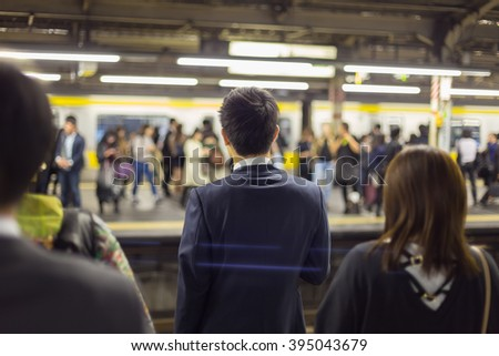 Passengers traveling by Tokyo metro. Business people commuting to work by public transport in rush hour. Shallow depth of field photo.  - stock photo