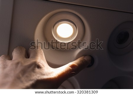 Passengers using the hand to turn off lights on the switch board on the plane. - stock photo