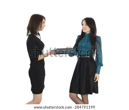 Passing business item. Two young women formal style dressed passing business notepad to each other on white background