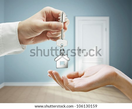 passing keys against backdrop of blue room - stock photo