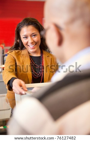 Passing over credit card to shop assistant after shopping - stock photo